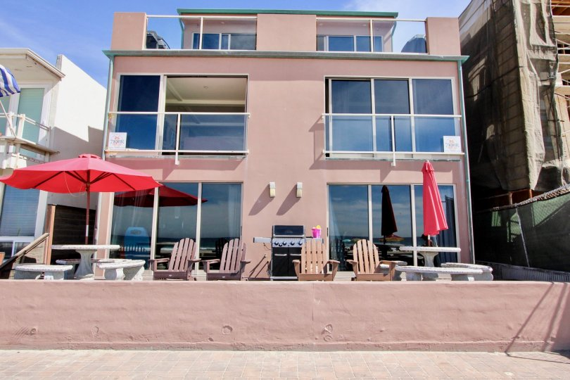 A deck with chairs, tables, and a grill at Jersey in Mission Beach, CA
