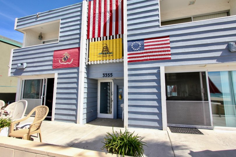 The exterior of a four unit apartment building with flags displayed and lawn furniture at MB Townhomes complex.