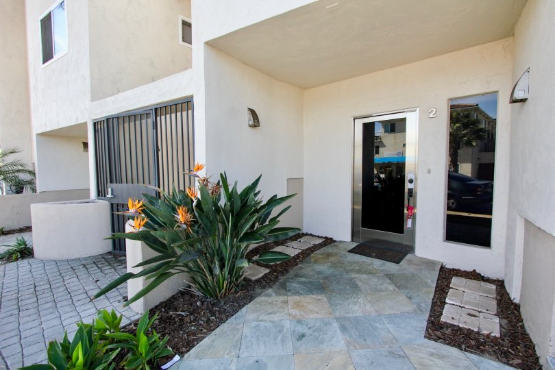 An entryway with glass doors and tropical plants at Mission Beach Villas