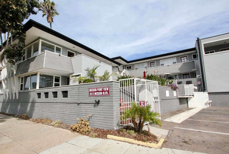 The exterior of the blue Mission View Point apartment complex with off-street parking and a privacy fence.