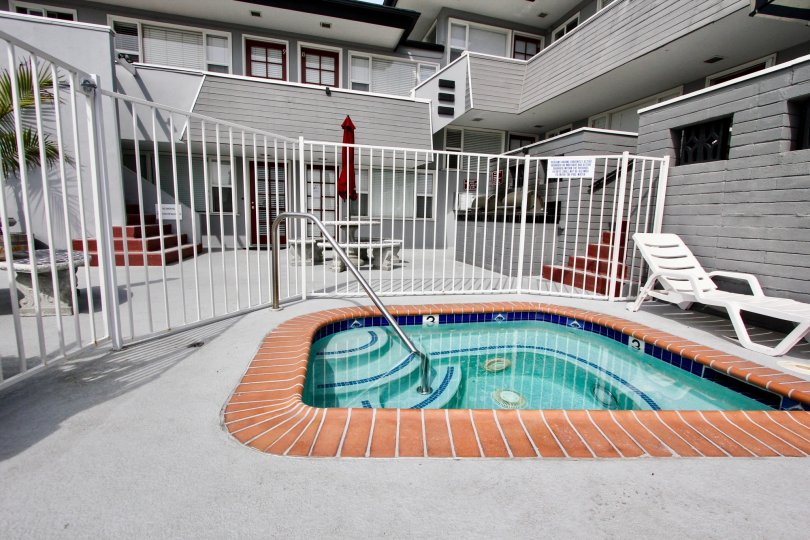 A single white lounge chair sits near a hot tub at Mission View Point.