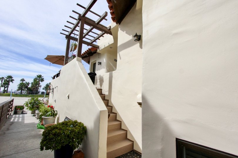 A narrow outdoor staircase on a white house in sunny Ocean Blue, Mission Beach, California