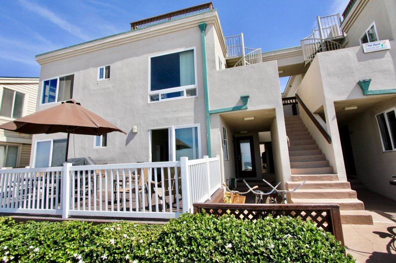 Two story building with a white railing with plants out front in Ocean Front Breakers at Mission Beach CA
