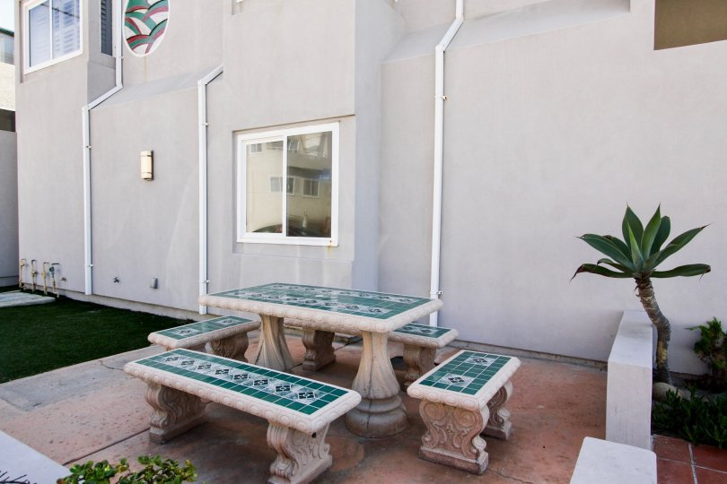 A tiled patio set with deck and palm trees at Ocean Front One