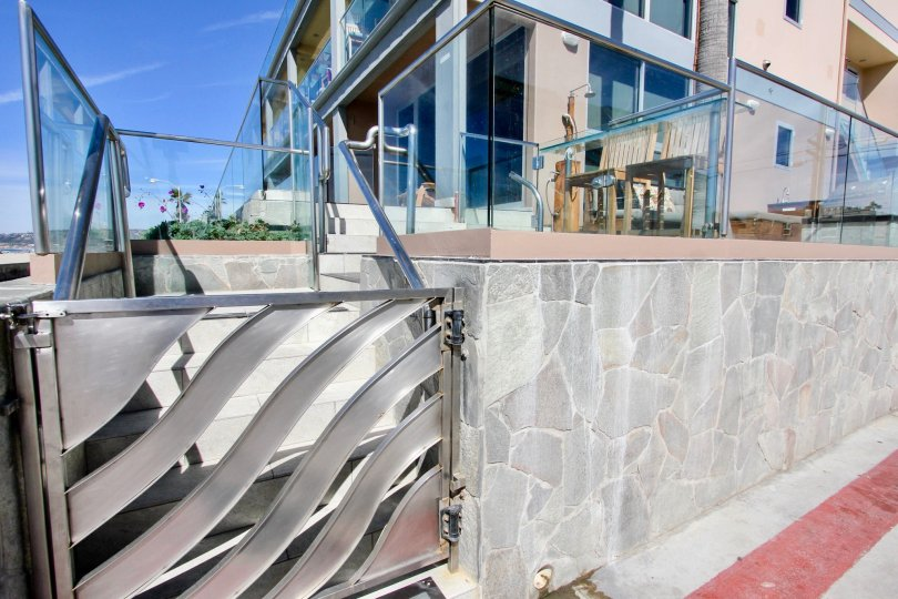 A gateway with glass railing and a stone wall in San Juan Condominiums