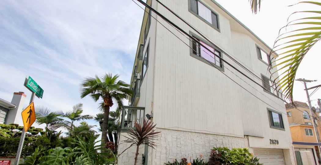 A white wood sided apartment home fronted by palm trees on Cohasset in The Fijian community.