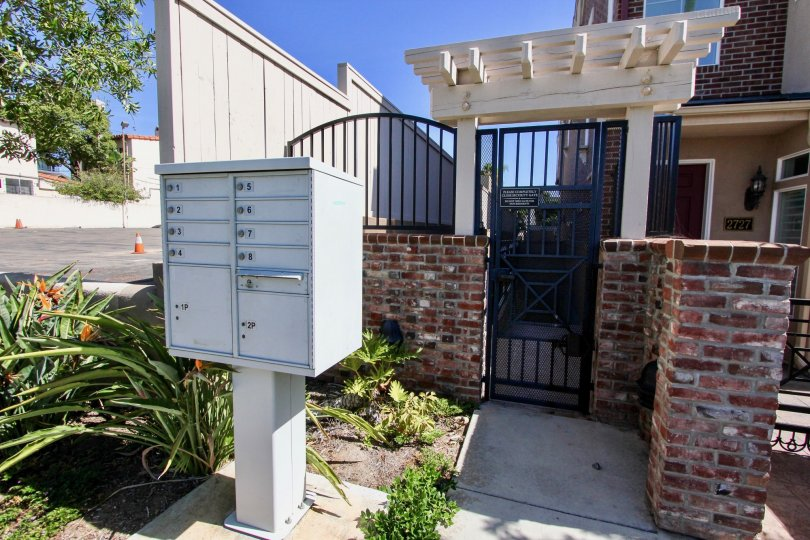 The entrance to a house with a mailbox and some bushes on front during a sunny day in Cambridge Square, Mission Hills, CA