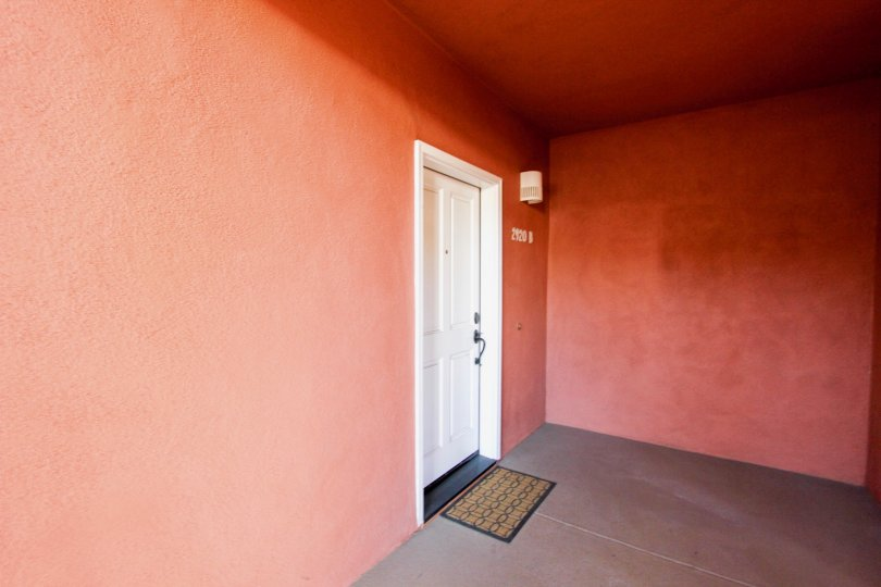 A door is covered the wall painted by red color and numbered the house as 2120