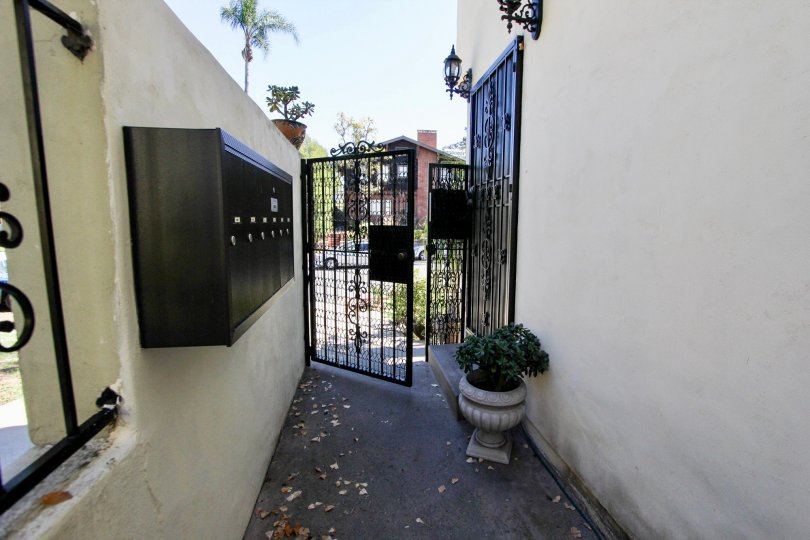 Narrow walkway with community mailboxes leading to a gated entrance to the Las Casas De Juan community in Mission Hills, CA