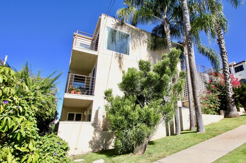 3 Story condominium building Mission Hills, California, with two decks, flanked with palm trees on a sunny day.