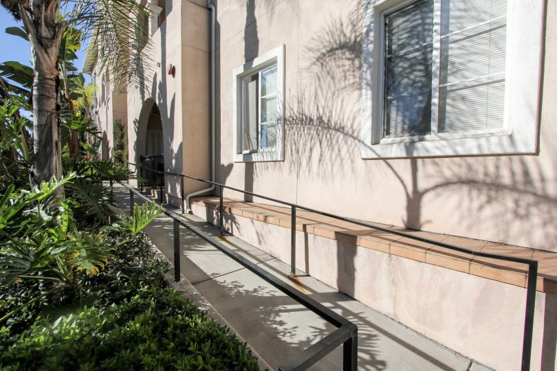 Gray paved sidewalk lined with plants at villa Portofino on Front in Mission HIlls CA