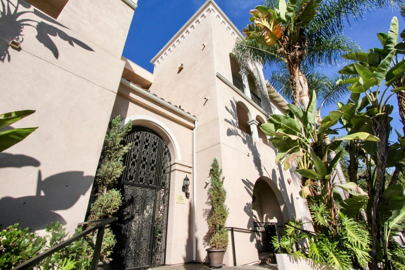 A luxurious building with very tall palm trees at the front during a sunny day in Villa Portofino on Front, Mission Hills, CA