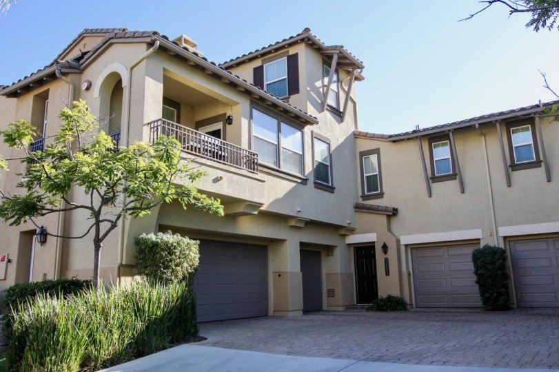 Courtyards at Escala in Mission Valley California are beautiful multi-level beige and brown stucco homes with garage space, balconies, and luscious green plants surrounding the area
