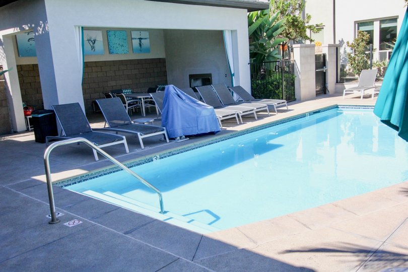 Large blue swimming pool lined with lawn chairs inside Frame and Focus in Mission Valley ca