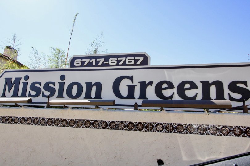 A sunny day in the area of Mission Greens, main sign, trees