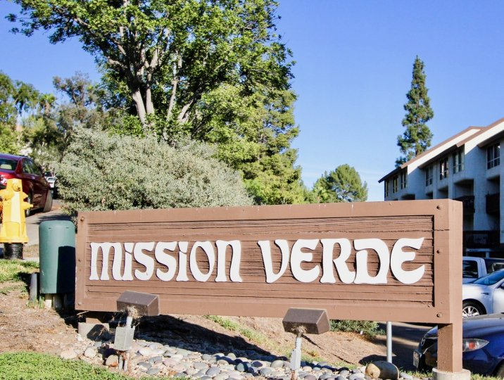 Mission Verde entrance including landscape, buildings, and parking area.