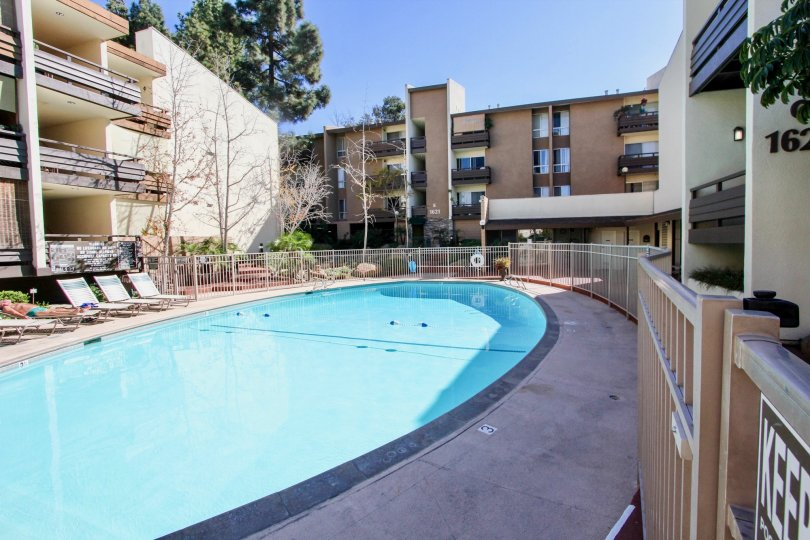 A large, oval pool sits in between three residential buildings at the Mission Village condos