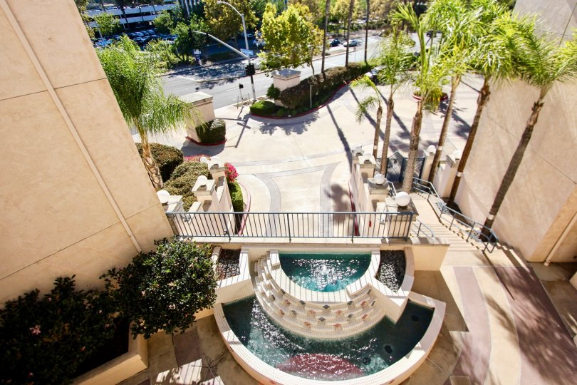A Birds-eye view of palm trees and a fountain at River Scene community in Mission Valley, CA