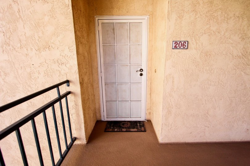 Still life image of a white front door of apartment 206 in the River Scene neighborhood