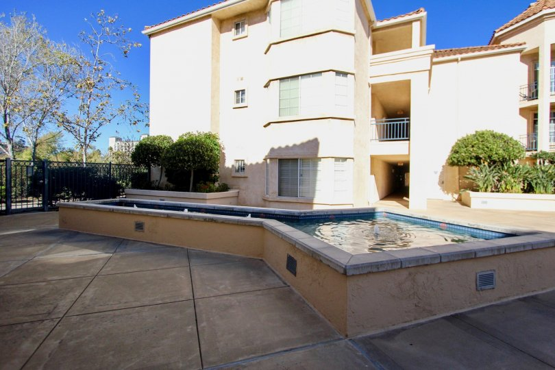 Three story, tan apartment building with swimming pool in River Scene, Mission Valley, CA