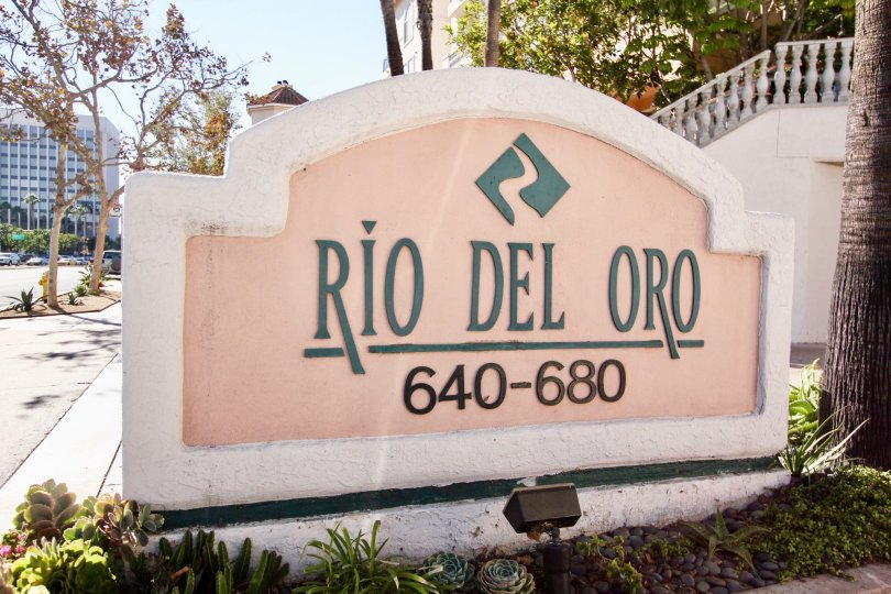 A sign that says Rio Del Oro behind a flowerbed at Rivery Scene in Mission Valley California