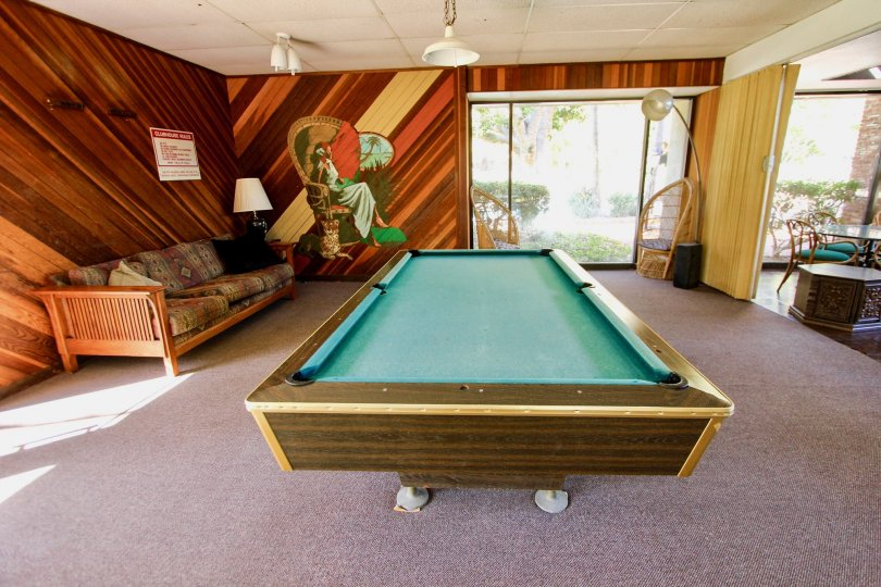 Pool table in a room at The Bluffs in Mission Valley, CA. Daytime. Room contains carpet, a futon, and a moveable room divider.