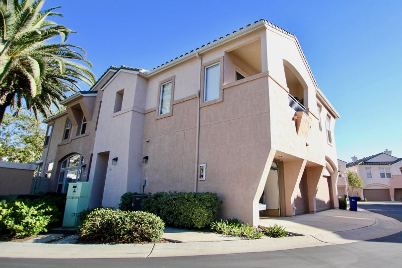 Sunny outdoor view of palm tree and two storey home in Union Square community in Mission Valley, CA