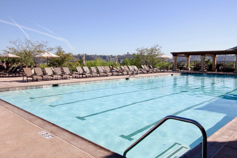 Large blue pool lined with many sun chairs at Verandas at Escala in Mission Valley CA