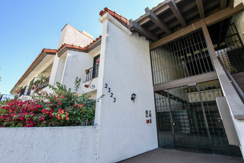A sunny day in the area of Casa Monterey, outside, gated entrance, flowers, stairs, balcony