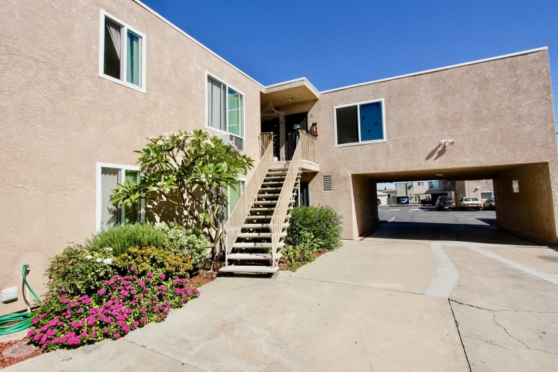 An open drive with a small garden next to a staircase leading up to an apartment door in Normal Heights in California.