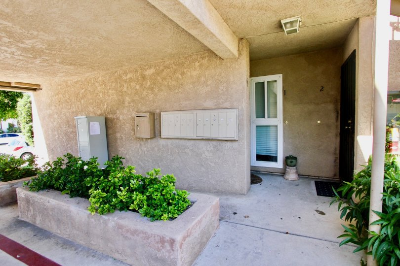 Stucco building, condo/townhome/appartment, main floor, mailboxes, landscaping,