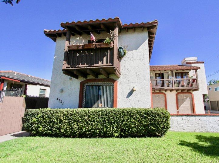 A sunny day in the area of Hawley Villas, bushes, condos, grass, fence, balconies