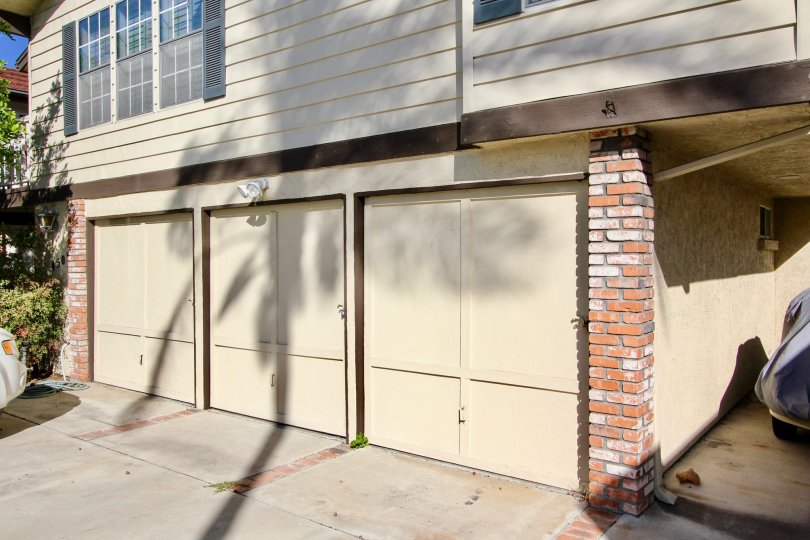 Single car garage units with decorative doors below windows with stylish shutters at Hermitage II