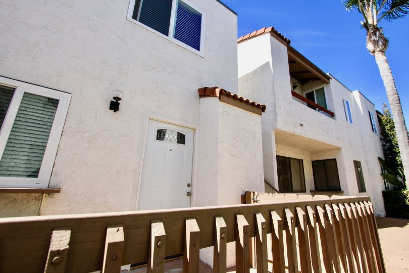 The exterior of a unit at the white stucco Mission Villas condo complex under a blue sky.
