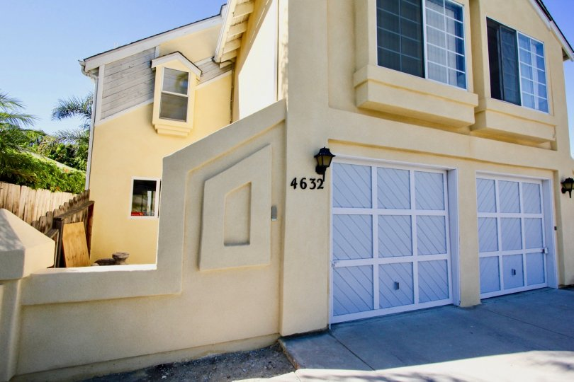 A beautiful yellow home with two garage doors located in the Normal House II Community.