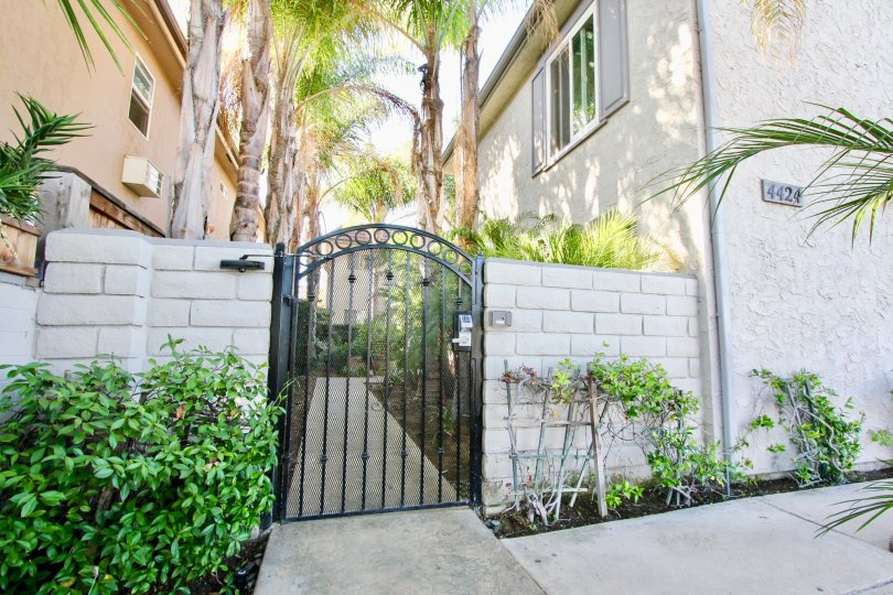 Security gate leading to the lush and well tended gardens and common walkway between the homes in Palm Villas of Normal Heights, California