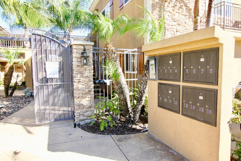 A sunny day in the area of Stone Manor, mailboxes, gate, palm trees, stones, sidewalk, condos