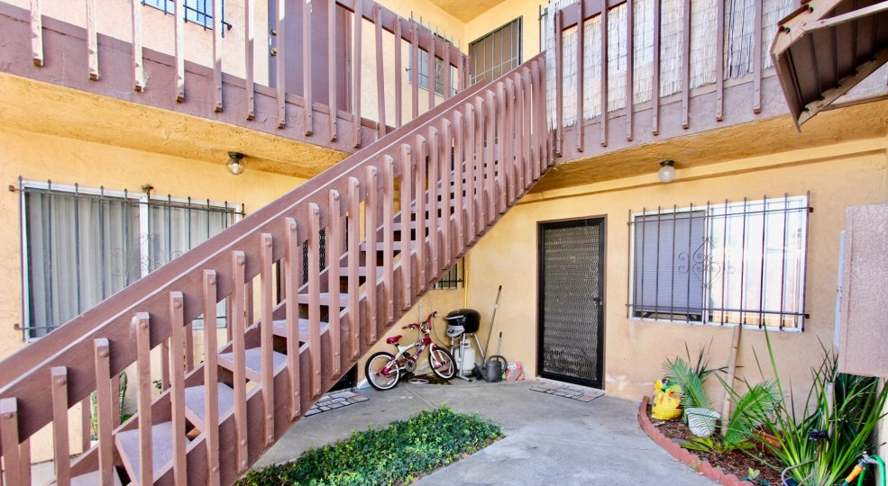 A staircase leads up a floor in an apartment block in Normal Heights with a bicycle leaning against a wall.