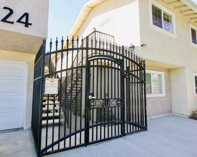 A sunny day in the area of The Bentley, gated entrance, stairs, sidewalk, windows