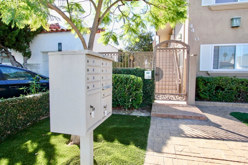 Community mailboxes and gated secure entryway with manicured lawns and shrubs at Utah West Villas