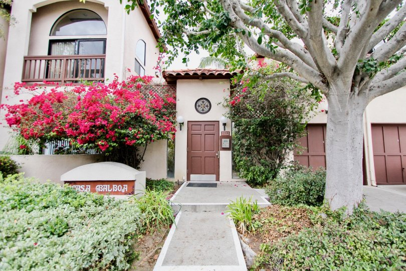 A 2 story, cream colored home with brown detailing and colorful landscaping in Casa Balboa, North Park, California.