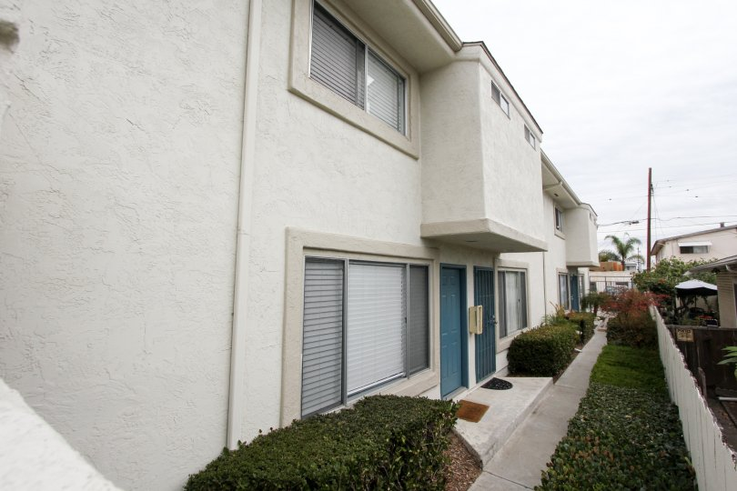 Walkway of an apartment building in Casa Diego II, North Park, California showing entrances and windows of individual units and shrubbery.