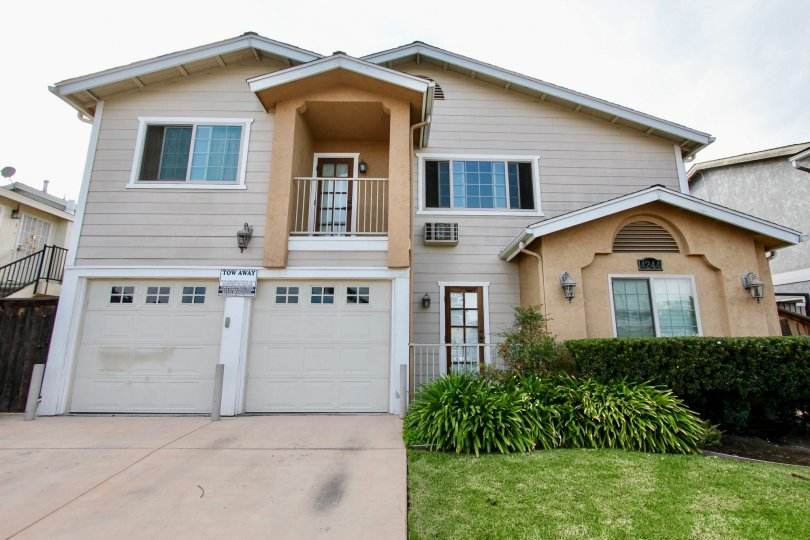 Two story building with gray garages with bushes inside Cherokee Villas at North Park CA