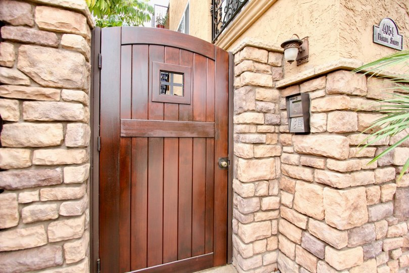 The outside private entrance at Florida Terrace with a call box, wooden gate, and stone wall.