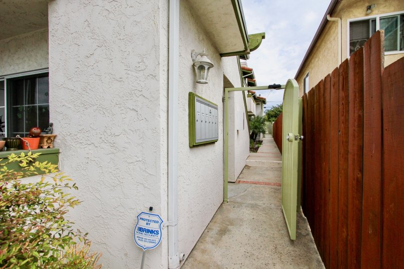 A sunny day in the area of Grim Townhomes, doorway, walkway, wooden fence, mailbox