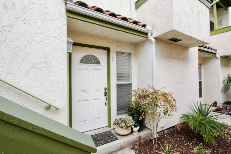 View of a main door of a house with green frame and with white door in the Grim Townhomes