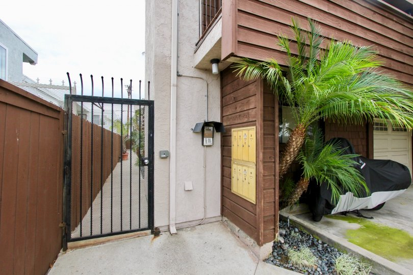 The exterior of Idaho Street Condominiums showing the gated enteryways palm trees and garage door
