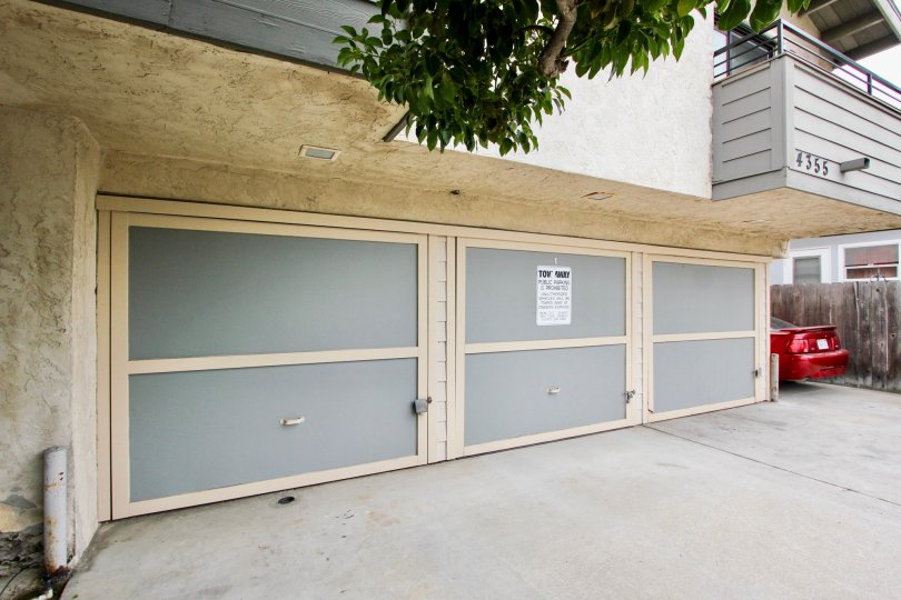 Closed garage doors and parked red car in Kentwood Condos in the city of North Park, CA