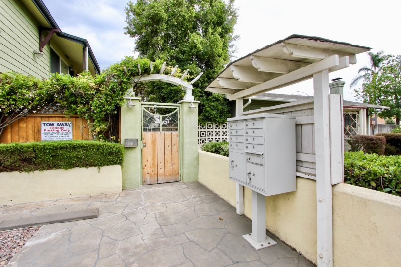 A gray metal mailbox sits under an awning near a gravel parking lot outside of an olive green apartment building in the Magnolia Walk community in North Park California