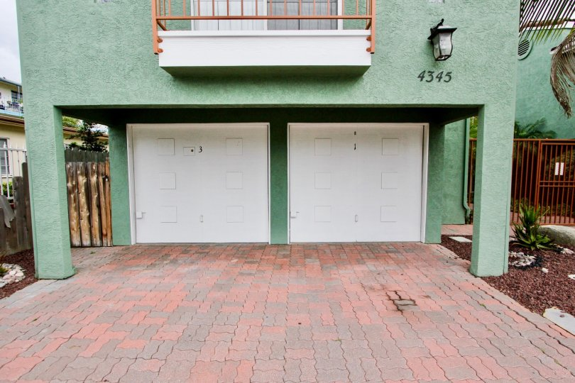 The exterior of 4345 Majestic Palms in North Park showing a balcony and garage doors